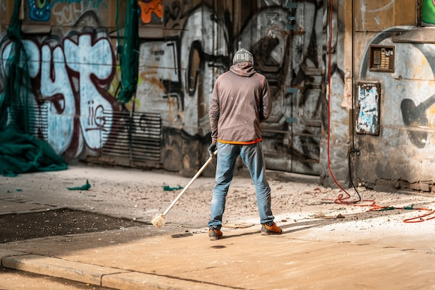 Limpando as ruas da cidade enquanto repara a fachada da casa