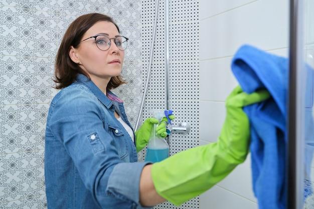 Limpando banheiro, mulher em luvas com pano e detergente, lavando e polindo o vidro do chuveiro