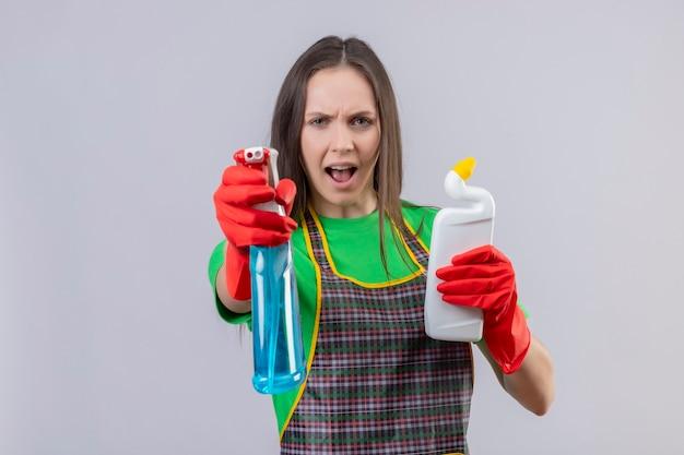 Limpando mulher jovem usando uniforme com luvas vermelhas segurando um agente de limpeza e segurando um spray de limpeza na parede branca isolada