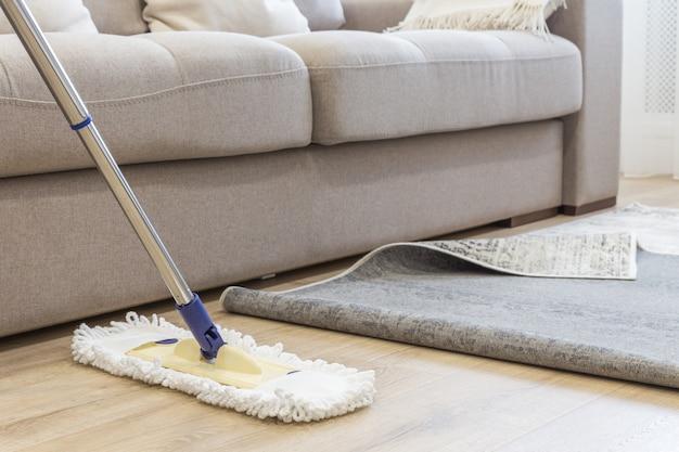 Limpando o chão com esfregão sob o tapete na sala de estar