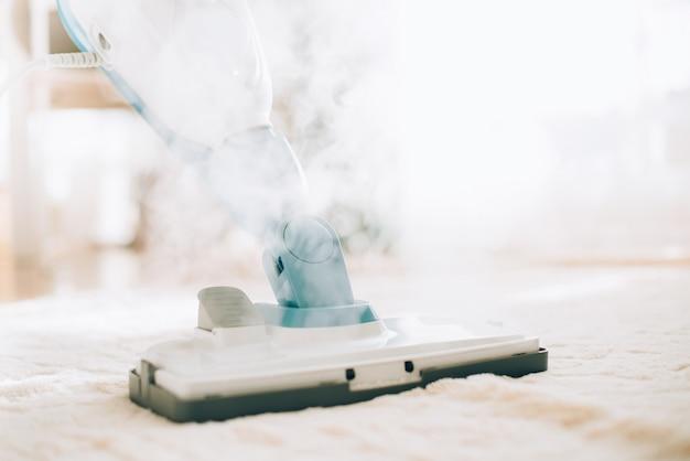 Limpando o chão com limpador a vapor. conceito de serviço de limpeza