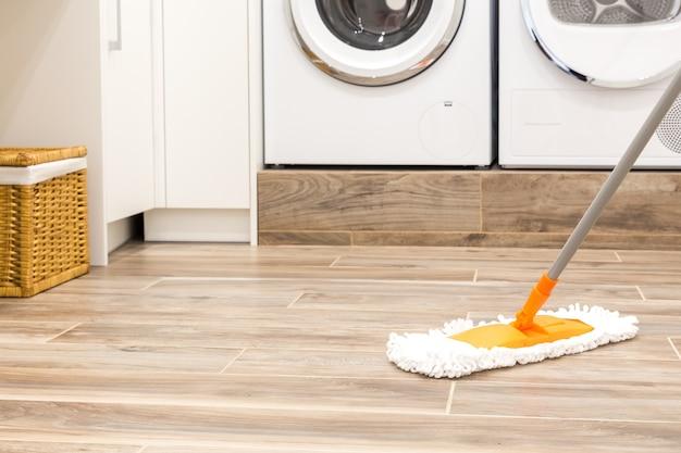 Limpando o chão na lavanderia em casa moderna