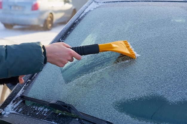 Limpando o pára-brisa do carro do gelo