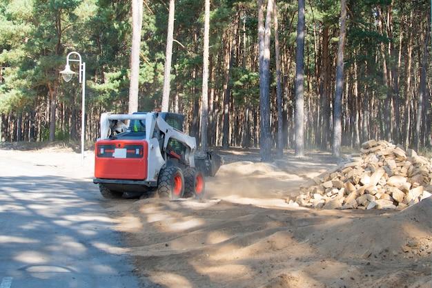 Limpando o parque, fazendo a manutenção das trilhas do parque. equipamento especial, uma escavadeira funciona