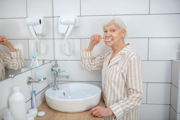 Limpando os dentes. . mulher idosa escovando os dentes no banheiro