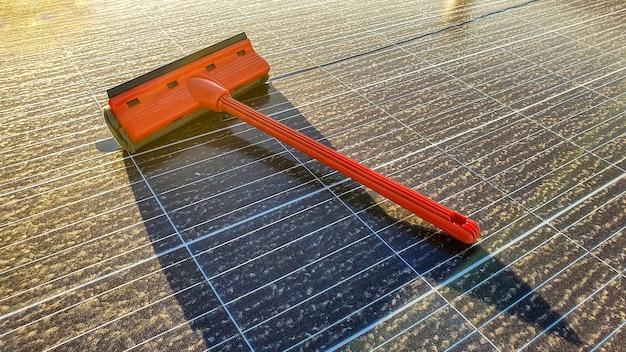 Limpando painel solar sujo ao pôr do sol