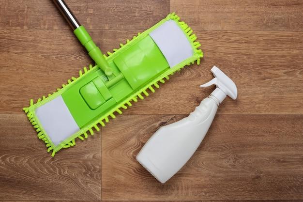 Limpando produtos. esfregão de plástico verde, frasco de spray no chão de madeira. desinfecção e limpeza em casa. vista do topo