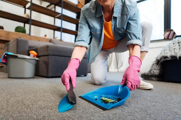 Limpando todas as superfícies. limpador de trabalho pesado usando pá azul e vassoura para coletar sujeira do piso do carpete
