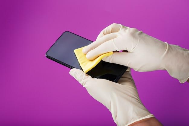 Limpando um smartphone com um guardanapo amarelo de sujeira e vírus em luvas de borracha em uma superfície rosa