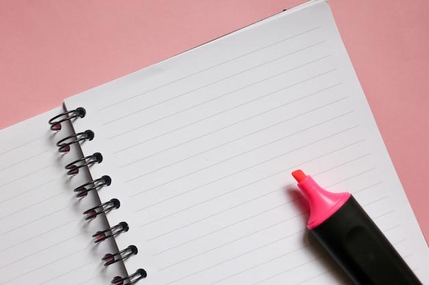 Limpar o bloco de notas com espaço de cópia e marcador rosa sobre fundo rosa