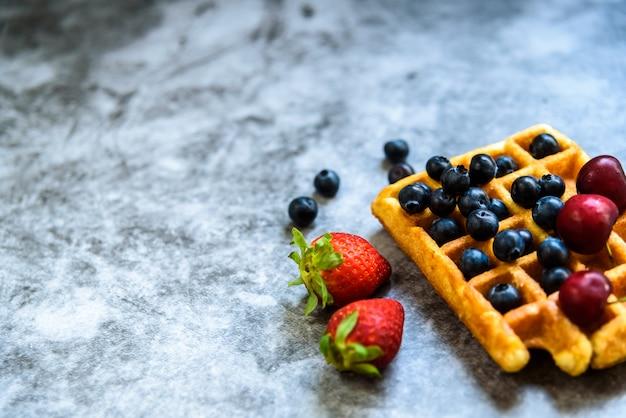 Limpar o fundo com espaço negativo para alimentos saudáveis e frutas antioxidantes e um waffle como junk food.