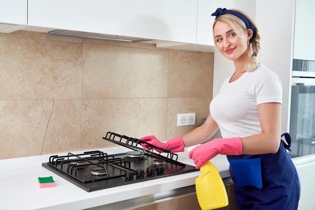 Limpar um fogão a gás com utensílios de cozinha, conceitos domésticos ou higiene e limpeza.