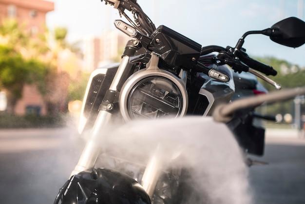Limpar uma motocicleta com água em alta pressão. conceito de limpeza de moto no posto de gasolina.