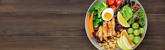 Limpe a comida com vegetais mistos e salada de frutas no fundo da bandeira de madeira