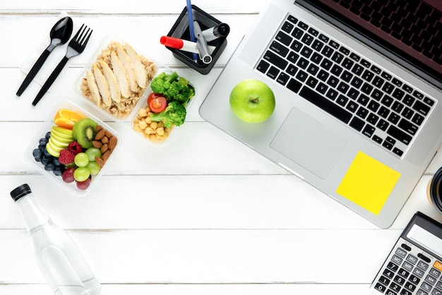 Limpe a comida saudável com baixo teor de gordura com o computador portátil na mesa de trabalho