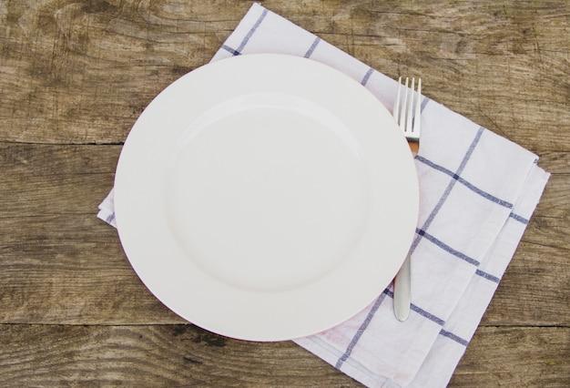 Limpe a placa branca vazia com a forquilha no guardanapo claro na tabela de madeira rústica.