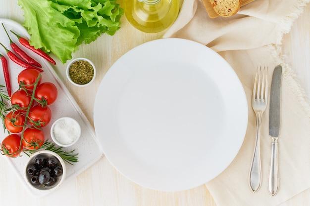 Limpe a placa branca vazia e legumes no fundo de madeira bege, vista superior