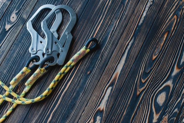 Limpe a superfície. equipamento de escalada isolado. parte do mosquetão deitado sobre a mesa de madeira.