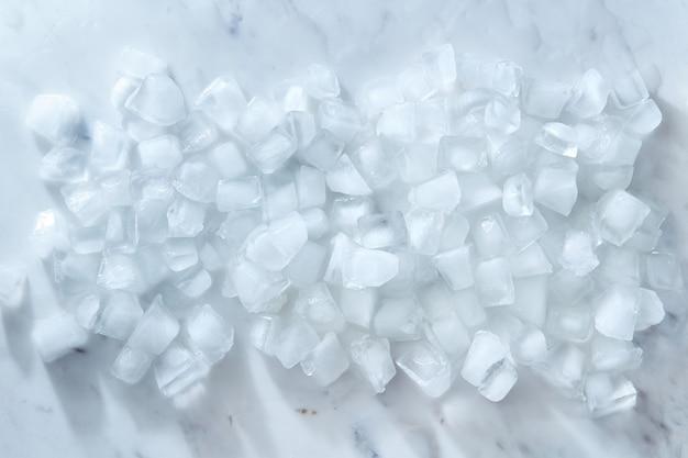 Limpe cubos de gelo frio em um fundo de mármore cinza