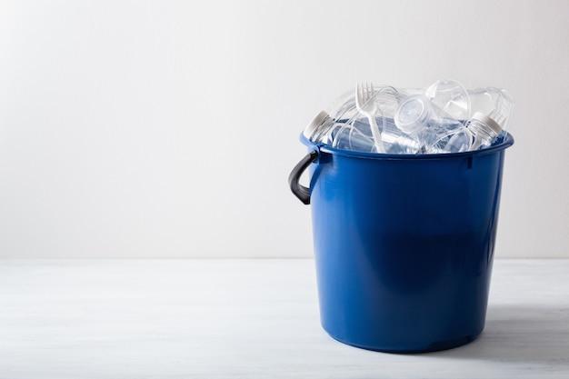 Limpe garrafas plásticas recicláveis, recipientes, copos na lata de lixo. reutilização de plástico para gestão de resíduos