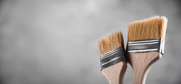 Limpe novos pincéis para pintura em fundo cinza de concreto borrado. feche com cópia de espaço vazio para o texto. banner para publicidade.