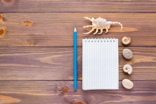 Limpe o bloco de notas aberto para escrever, lápis e concha sobre um fundo de madeira. vista do topo. copie o espaço. conceito de férias.