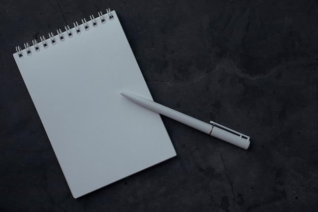 Limpe o bloco de notas e caneta em fundo escuro com textura. conceito de educação ou negócios, com espaço para texto. caderno com papel branco para escrever notas, vista superior.