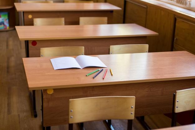 Limpe o caderno e lápis de cor em cima da mesa na sala de aula vazia.