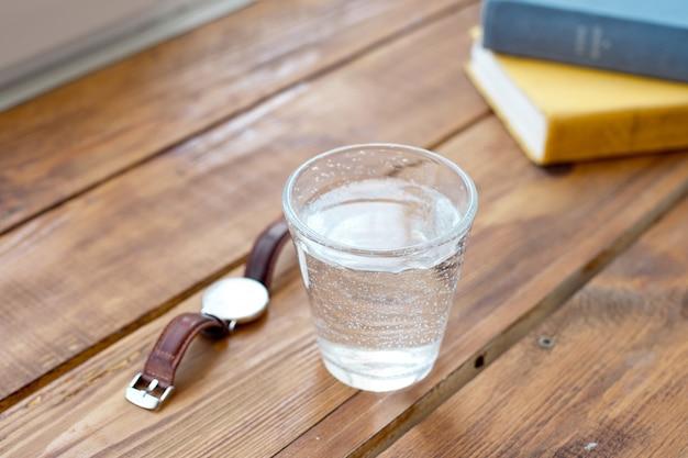 Limpe o copo de água em uma mesa de madeira enquanto lê os livros de trabalho de um relógio para lembrá-lo de levar regularmente à água um estilo de vida saudável.