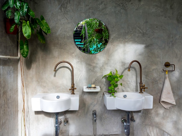 Limpe o interior do banheiro em estilo loft com duas pias brancas modernas, torneiras de latão, folhas verdes no vaso e espelho redondo na parede de concreto