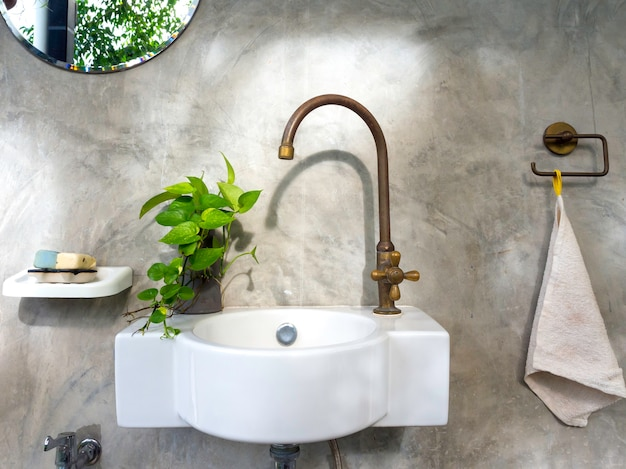 Limpe o interior do banheiro em estilo loft com pia moderna branca e torneira de latão, folhas verdes na panela e espelho redondo na parede de concreto