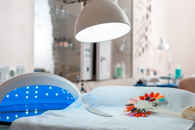 Limpe o local de trabalho do especialista em beleza do nail master no interior do salão de beleza. ferramentas de extensão profissional de unhas lâmpada cosmética. mesa de manicure vazia com ninguém.