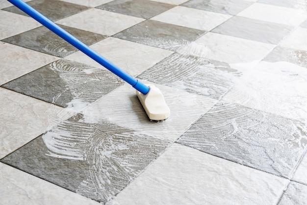 Limpe o piso de cerâmica com uma escova de cabo longo.