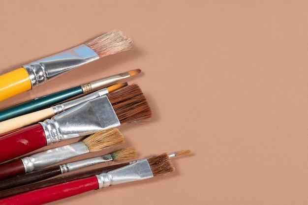 Limpe os pincéis de artesanato em um fundo ocre com espaço de cópia
