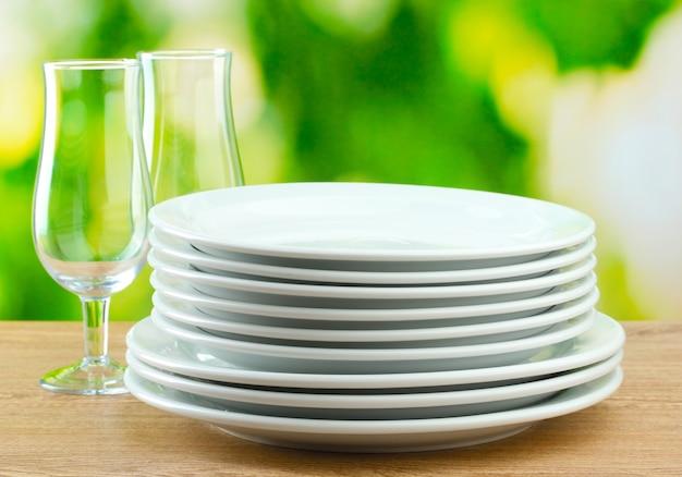 Limpe os pratos na mesa de madeira no verde