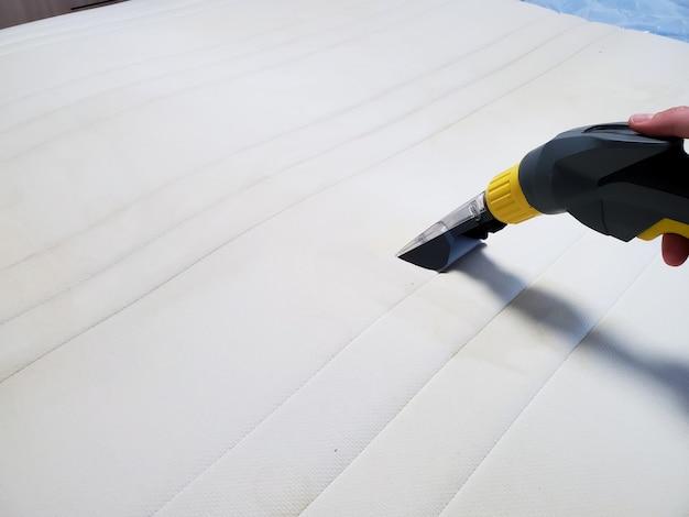 Limpeza a seco do colchão na cama com equipamento profissional