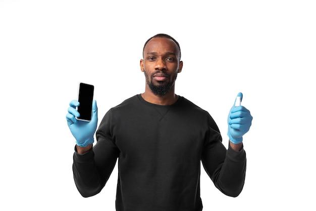 Limpeza. como o coronavírus mudou nossas vidas. homem desinfetando dispositivos na parede branca. prevenir pneumonia, continuar em quarentena, ficar em casa. tratamento covid, em recuperação.