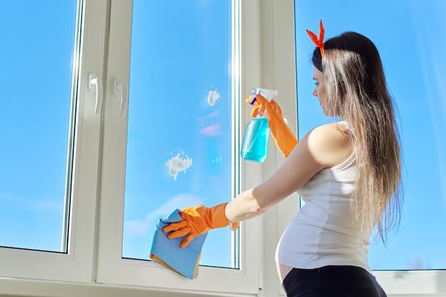Limpeza da casa, bela jovem de luvas com detergente e vidros para lavar roupas