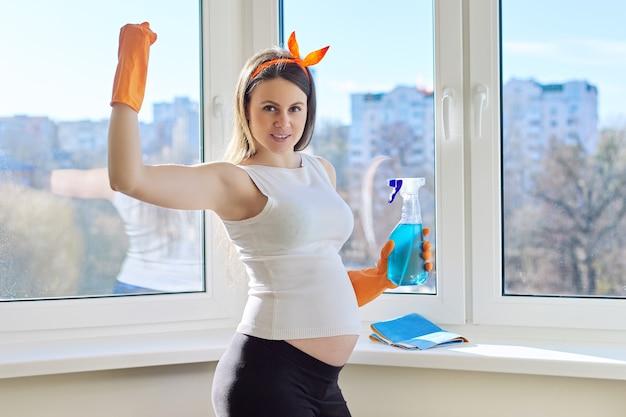 Limpeza da casa, bela jovem grávida em luvas com pano e detergente posando, olhando para a câmera, perto da janela limpa lavada no quarto