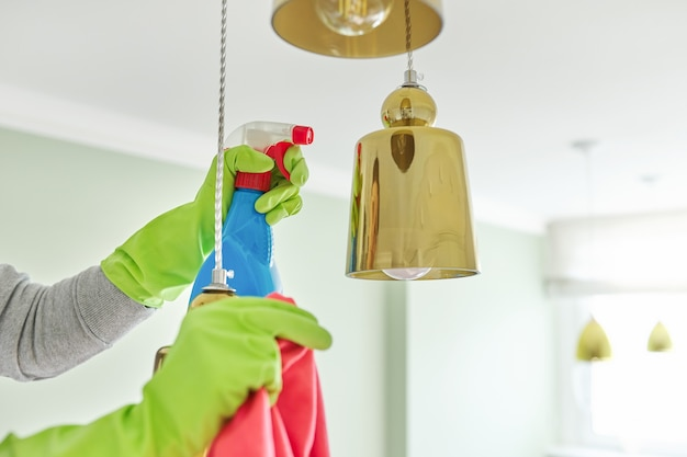 Limpeza da casa, close-up das mãos com detergente de pano, lâmpada de limpeza e polimento, lustre
