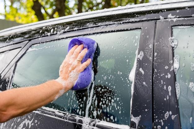 Limpeza de automóvel de carro usando esponja e sabão