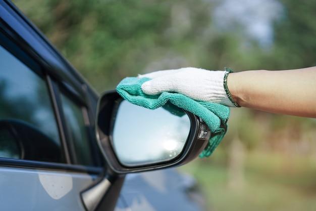Limpeza de carro com pano de microfibra de cor verde ao ar livre nas férias.