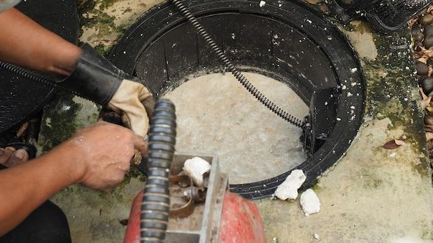Limpeza de drenos. encanador que repara caixa de gordura entupida com máquina de trado. manutenção do sistema de esgoto e caixa de gordura por encanador profissional. usando a serpente de trado para consertar e desentupir um ralo.