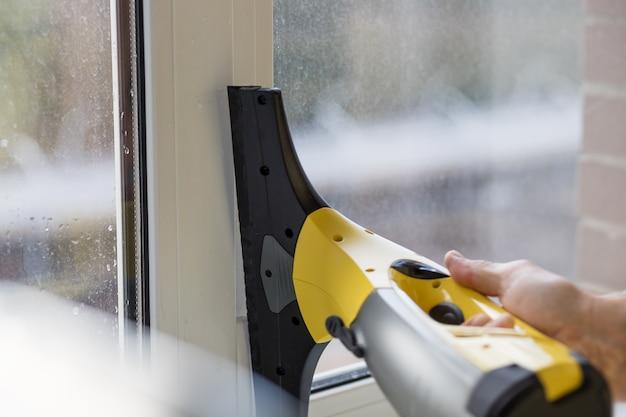 Limpeza de janelas com aspirador de pó elétrico. imagem da limpeza da casa da primavera. lavagem da janela com um aspirador de pó. mão com aspirador de pó profissional portátil