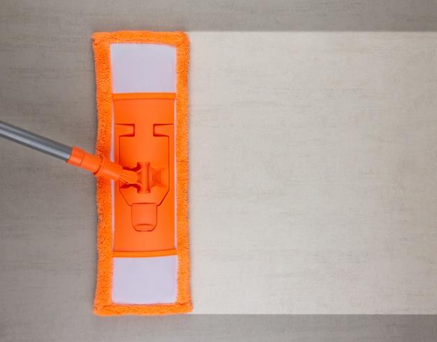 Limpeza de piso cerâmico cinza com esfregão laranja, vista superior com espaço de cópia