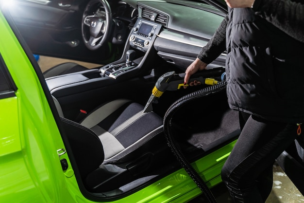 Limpeza de salão de automóveis, lavagem a seco com aspirador. uso profissional de um aspirador de pó a vapor para remover manchas