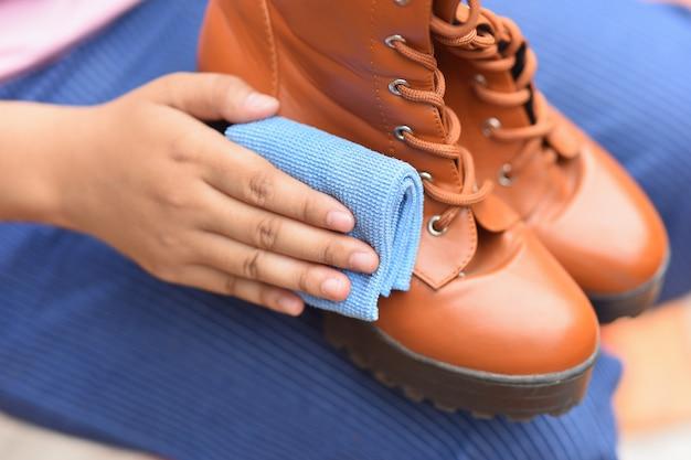 Limpeza de sapatos de couro com um pano de polimento
