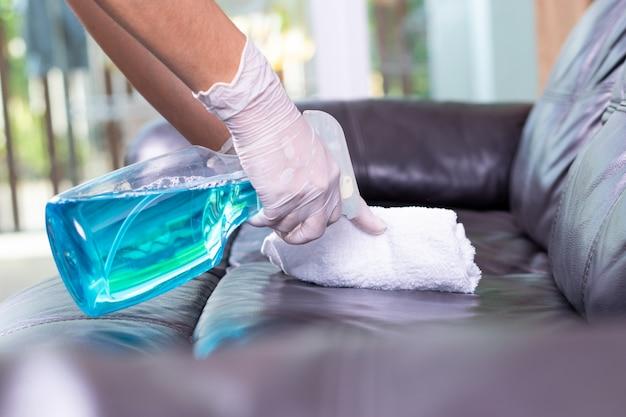 Limpeza de sofá de couro em casa para proteção covid-19. covid-19 ou conceito de surto de coronavírus.