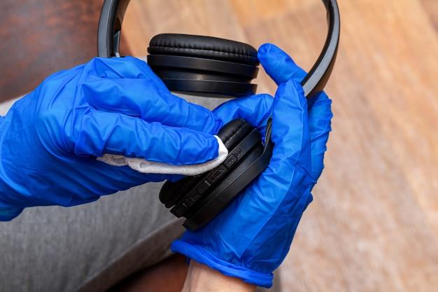 Limpeza, desinfecção, limpeza de fones de ouvido com a mão na luva e guardanapo close-up