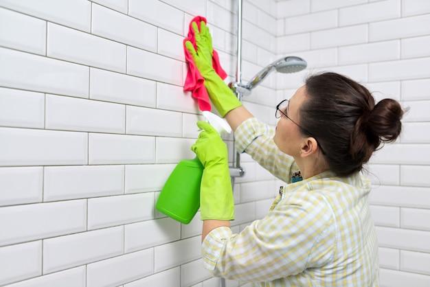 Limpeza do banheiro, dona de casa lavando a parede de azulejos brancos com detergente e pano, copie o espaço. conceito de higiene, pureza, limpeza